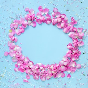 Elevated view of rose petals forming circular frame on blue background