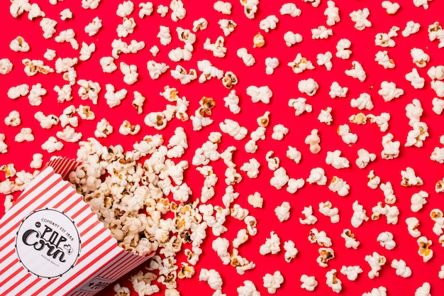 An elevated view of salty spilled popcorns from box on red backdrop