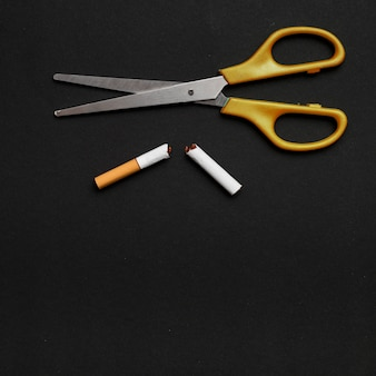 Elevated view of scissor and broken cigarette over black background