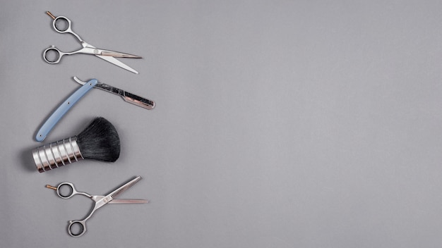 Elevated view of scissors, shaving brush and razor over grey backdrop