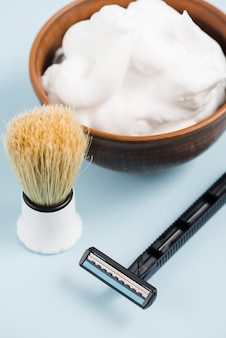 An elevated view of shaving brush; razor and foam in wooden bowl against blue backdrop