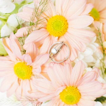 An elevated view of silver diamond wedding rings on pink gerbera flower