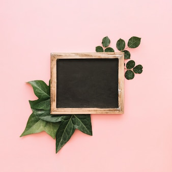 Elevated view of slate over tropical leaves on pink surface