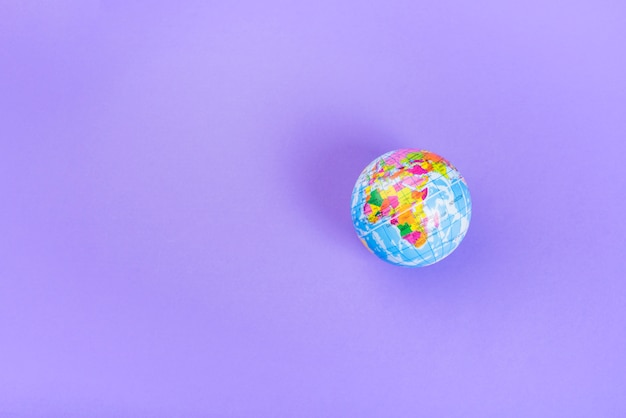 Elevated view of small plastic globe against purple backdrop
