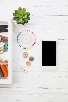 Elevated view of smartphone; clothes peg; button and sewing pin on wooden background