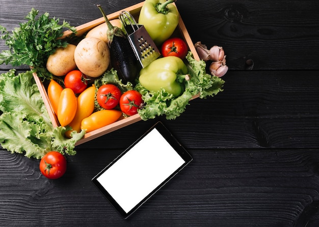 Elevated view of smartphone near vegetables in container on black wooden surface