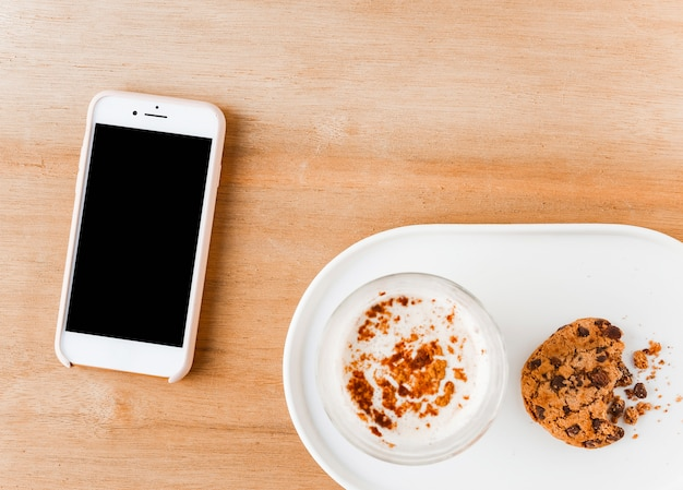 Elevated view of smartphone with coffee glass and eaten cookies