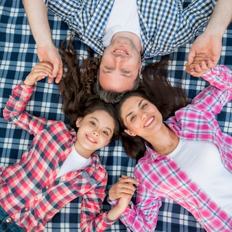 Elevated view of smiling family lying on checkered blanket