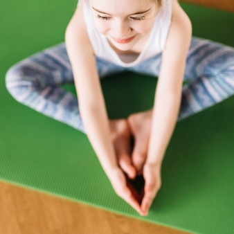 Elevated view of smiling little girl child doing yoga on green mat