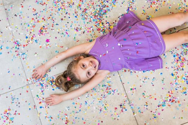 Punto di vista elevato della bambina sorridente che si trova sul pavimento con i coriandoli