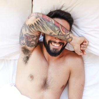 Punto di vista elevato di un giovane senza camicia sorridente che si trova sul letto
