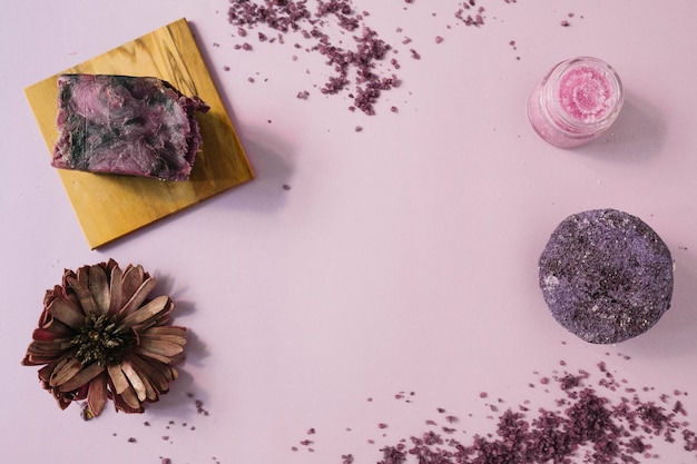 An elevated view of soap bar; dried flower and body scrub against pink background