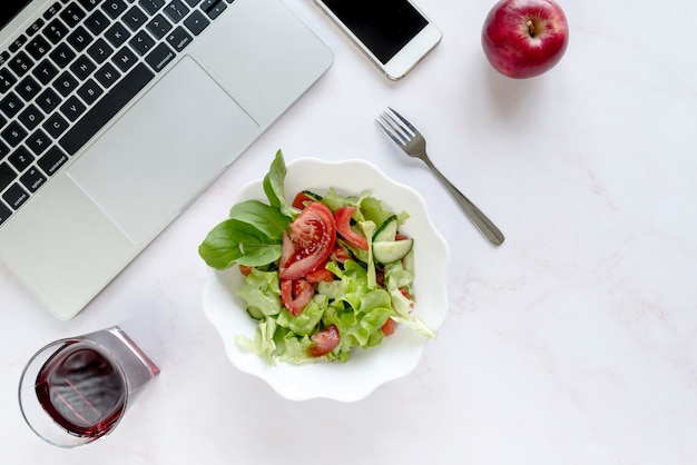 Elevated view of soft drink; bowl of salad; apple and fork near electronic devices over white background