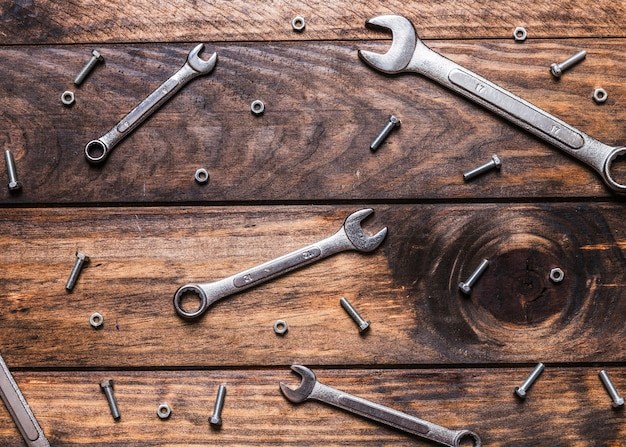 Elevated view of spanners and screws on wooden background