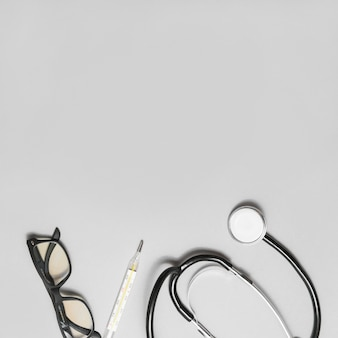 Elevated view of spectacles; stethoscope and thermometer on grey background