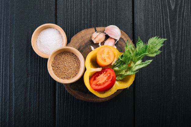 Elevated view of spices and ingredients on black textured wooden background
