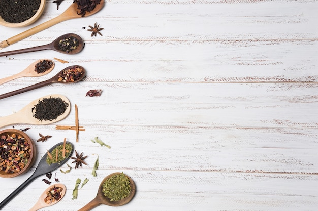 An elevated view of spices on wooden spoon over the white wooden table
