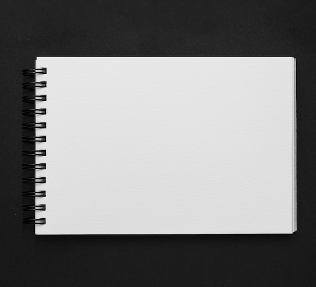 Elevated view of spiral notepad on black background