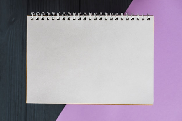 Elevated view of spiral notepad on colorful background