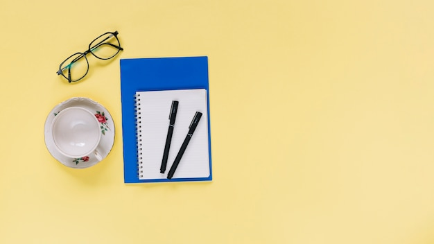 Elevated view of spiral notepad; cup and eyeglasses on yellow background