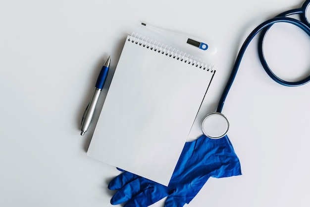 Elevated view of spiral notepad; pen; stethoscope; thermometer and gloves on white backdrop