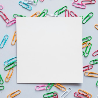 Elevated view of square shaped cardboard paper and many paper clips on grey background