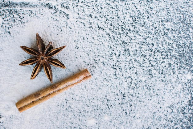 Elevated view of star anise; cinnamon stick and flour