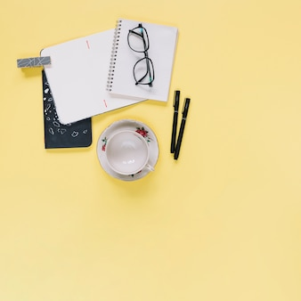 Elevated view of stationeries and empty cup on yellow backdrop