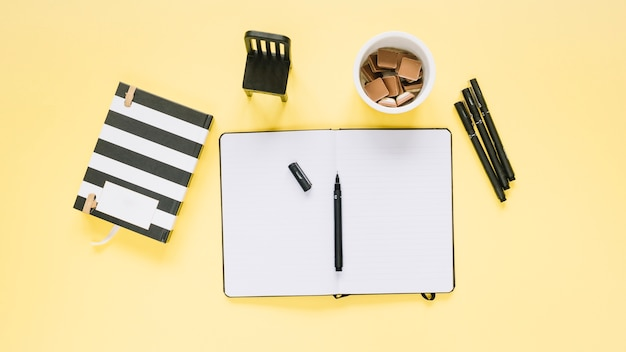 Elevated view of stationeries and glass of chocolates on yellow background