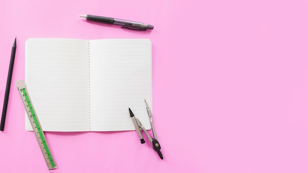 Elevated view of stationeries and open notebook on pink background