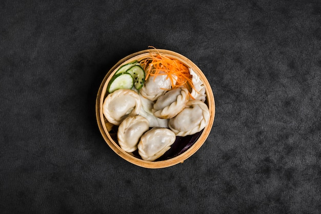 An elevated view of steam dumplings in steamer container on black texture background
