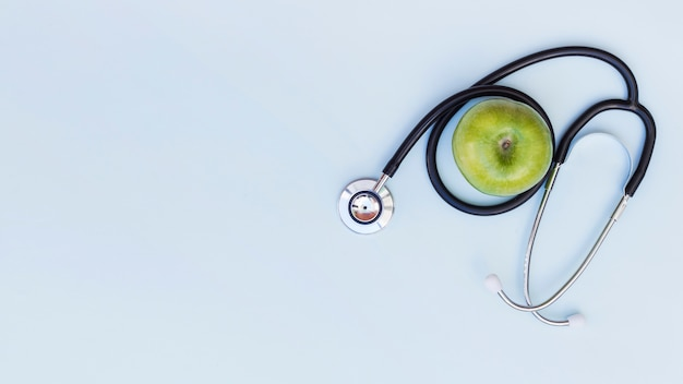 An elevated view of stethoscope around the green apple over blue background