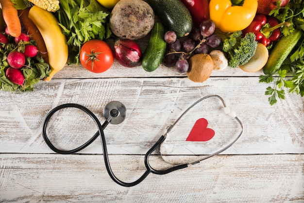 Elevated view of stethoscope with heart shape near fresh vegetables on wooden desk