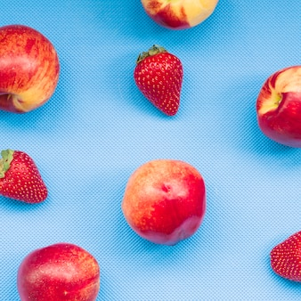 Elevated view of strawberries and apple on blue background