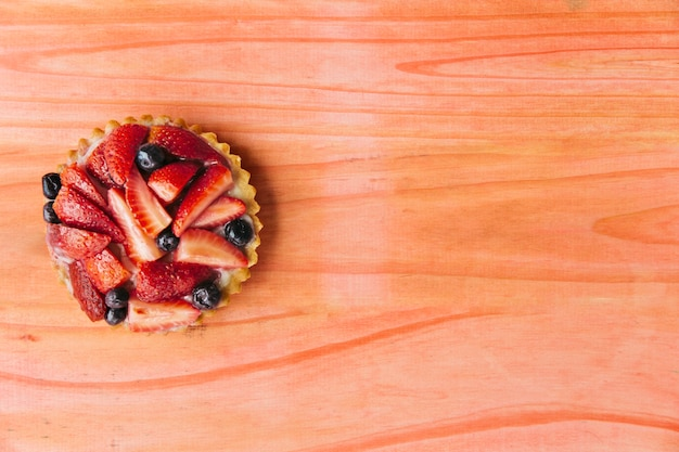 Elevated view of strawberry tart on wooden desk