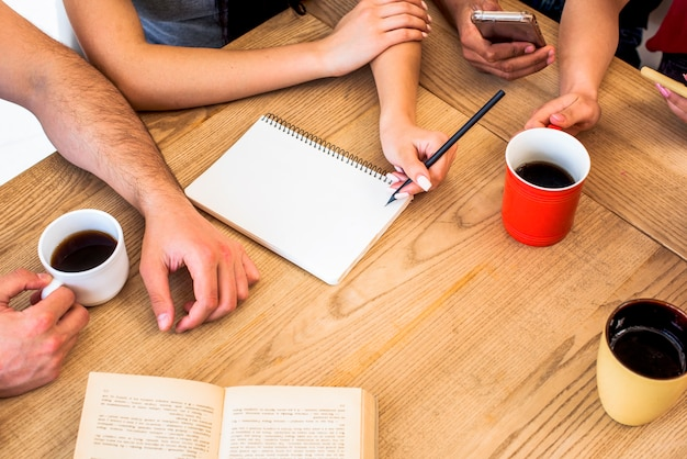 Elevated view of students with study materials and cups of coffee on wooden textured table