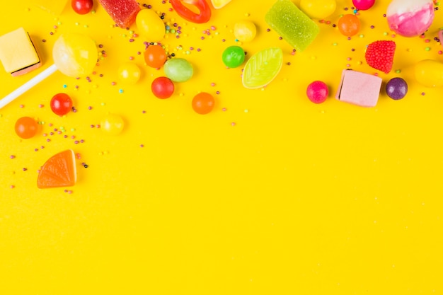 Elevated view of sweet candies on yellow backdrop
