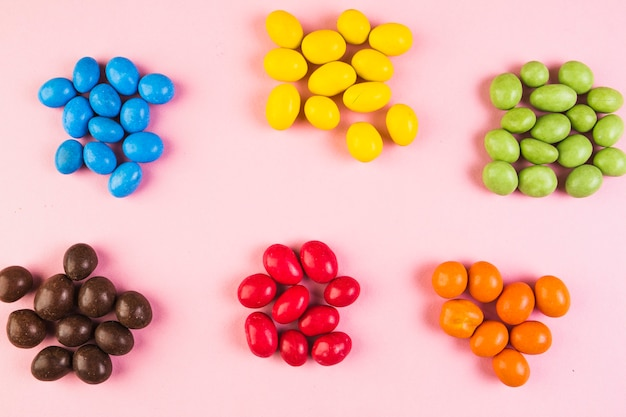 Elevated view of sweet colorful candies on pink backdrop