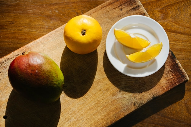 Elevated view of sweet lime and mango on chopping board