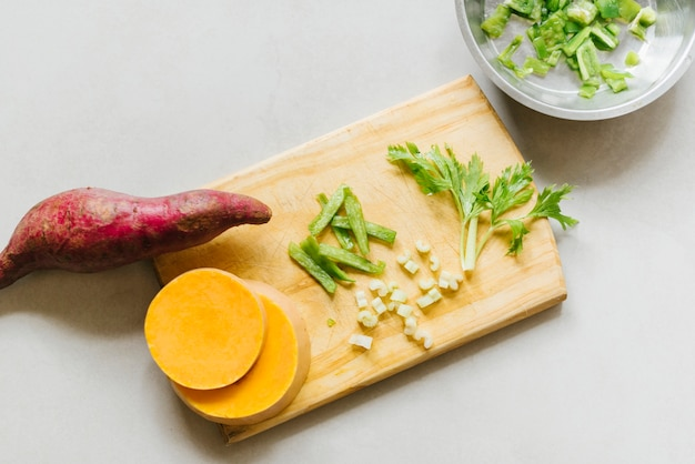 Elevated view of sweet potato; sliced pumpkin and celery on cutting board