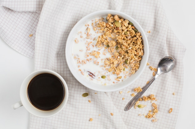An elevated view of tea cup; spoon and bowl of oats with pumpkin seeds on tablecloth