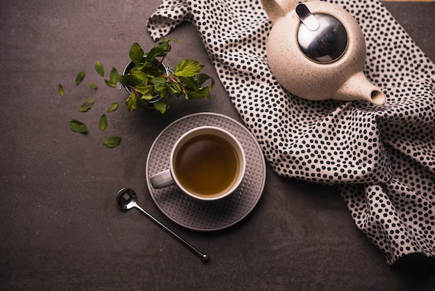 Elevated view of tea; leaves; teapot and polka dotted textile on table