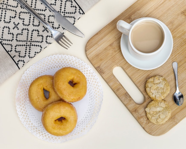Elevated view of tea with cookies and donuts