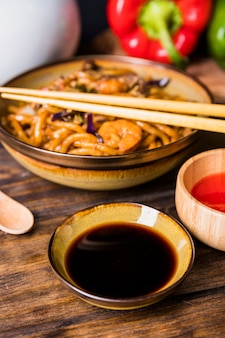 An elevated view of thai udon noodle with chopsticks and soya sauce on wooden table