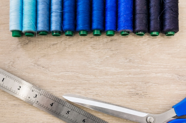 Elevated view of threads; scissors and scale on wooden backdrop