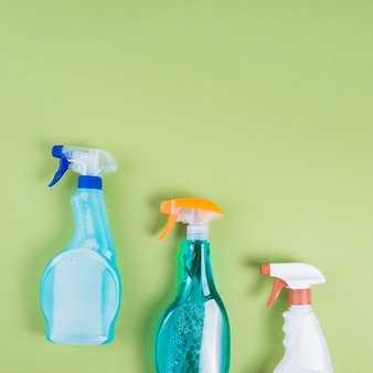 Elevated view of three spray bottles on green background