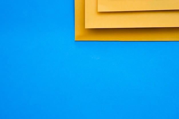Una vista elevata di tre craftpapers gialli su priorità bassa blu