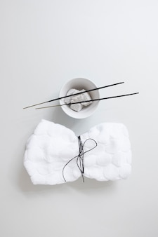 Elevated view of tied napkin near incense stick and pumice stone on white background