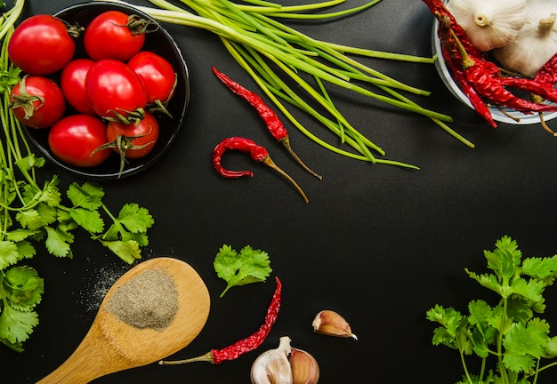 Elevated view of tomato; red chilies; spring onion; garlic; parsley and spices on black background