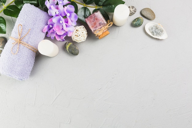 Elevated view of towel; candles; scrub bottle; flowers and spa stones on grey backdrop